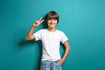 Smiling little boy in t-shirt showing Victory gesture on color background
