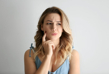 Portrait of thoughtful young woman on light background