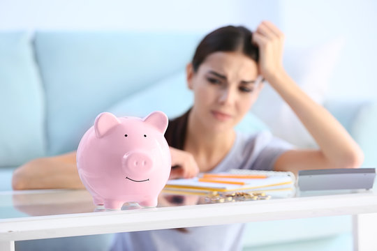 Piggy bank on table of young upset woman