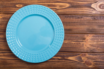 Empty blue plate on wooden table
