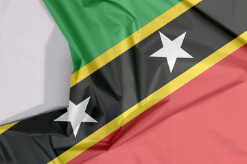 Saint Kitts and Nevis fabric flag crepe and crease with white space, yellow edged black diagonal with star, triangle green and red.