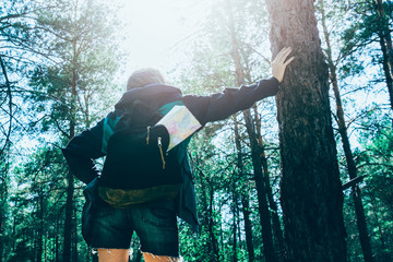 Beautiful young girl with equipment is standing in the forest. Backpack with map inside. Tourist...