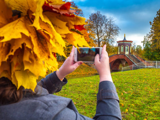 St. Petersburg in the fall. A girl is taking pictures of an autumn park in Pushkin. Russia in the fall. Tsarskoe Selo. Parks of the city of Pushkin. Petersburg autumn.