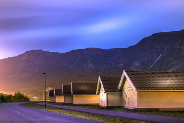 View of the coastline road Fv331 and the wooden houses at the port of  Skjolden villageat night, Luster, Norway.