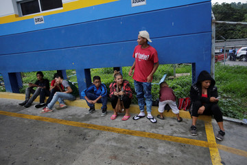 Hondurans wait to board a bus bound for San Pedro Sula after being sent back by Guatemalan authorities for crossing illegally in their bid to join a migrant caravan heading to the U.S., in Ocotepeque