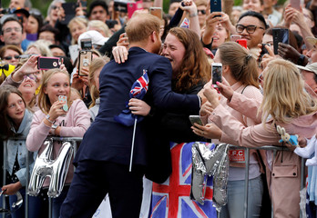 Britain's Prince Harry hugs a member of the public as he arrives at the Royal Botanic Gardens in Melbourne