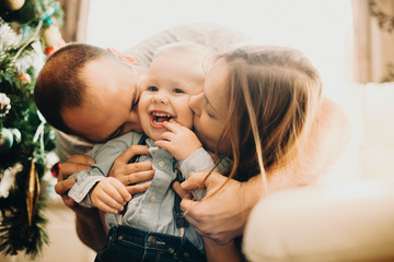 Parents kissing adorable toddler in cheeks