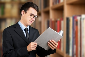 Young male student with notebooks at library
