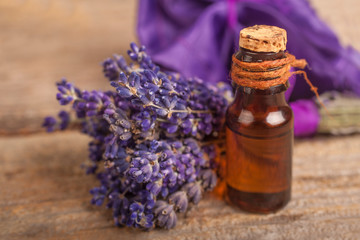 Essential lavender oil with a lavender flower on a rustic background