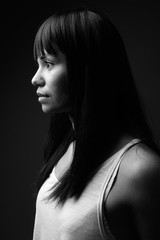 Young Asian woman against gray background in black and white
