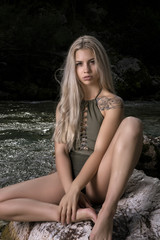 Supermodel woman in swimsuit sitting on the rock
