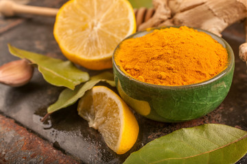 turmeric, lemon and laurel on a rustic surface, the concept of natural nutrition and medicine
