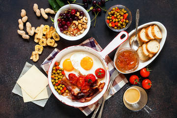 Breakfast including coffee, fried egg , becon. nut , muesli and bread . Top view