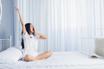 Woman stretching in bed after waking up, back view. Woman sitting near the big white window while stretching on bed after waking up with sunrise at morning, back view.