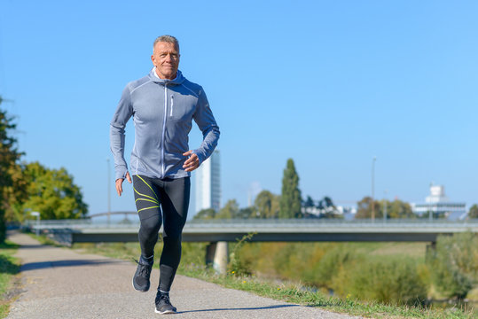 Gray smiling man running along river