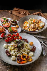 Spaghetti with pesto, salad with mussels and canapes with tomatoes. Mediterranean Kitchen. Vertical shot