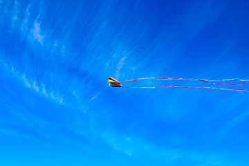 Colored 3D kite with long tails in a deep blue sky.