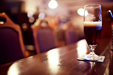 mug of dark beer in the interior of  pub / pint of beer with foam on a served table in  beer restaurant in Czech Republic