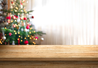 empty wood table top and blur of room with a christmas tree background, suitable for montage...