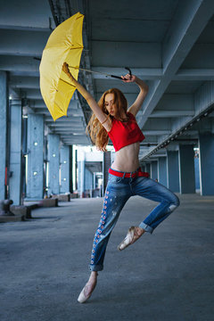 Ballerina is dancing with a yellow umbrella in jeans, T-shirt and pointe. Street performance. Modern ballet. Slender girl dancing on tiptoe. Red hair fly.