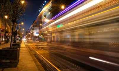 Light trails of a tram driving a street by night