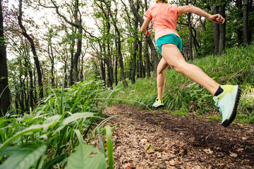 Young woman running in green forest. Endurance sport.