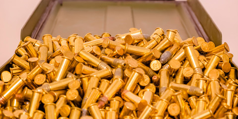 Shiny gold plated bullets inside an open container