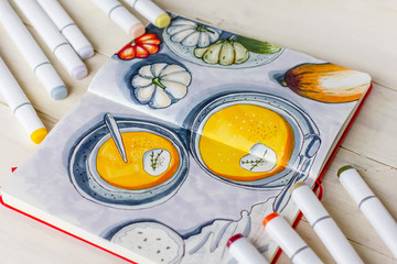 Sketch drawing by markers in sketchbook Pumpkin soup, flat lay