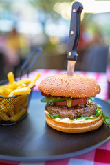 Tasty hamburger with grilled beef and chips on the plate