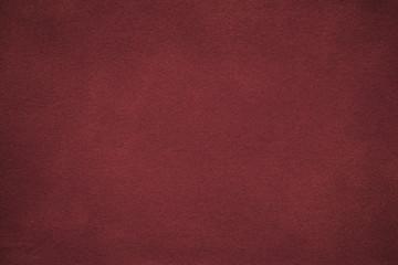 Background of dark red suede fabric closeup. Velvet matt texture of wine nubuck textile with gradient.