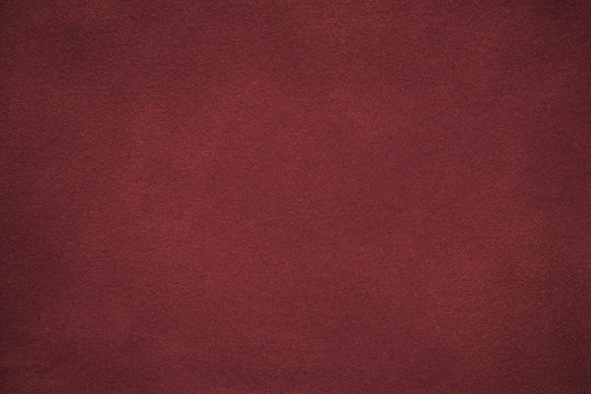 Background of dark red suede fabric closeup. Velvet matt texture of wine nubuck textile with gradient.