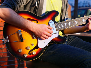 Male hands play an electric guitar on the street