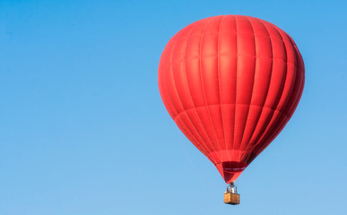 Red balloon in the sky. Aerostat. People in the basket. Fun. Summer entertainment. Romantic adventures.