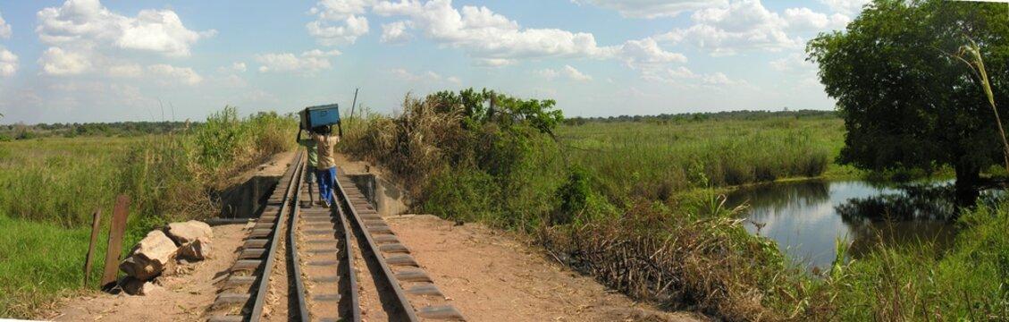 Carriers cross bridge along abandoned railroad, Katanga, Congo