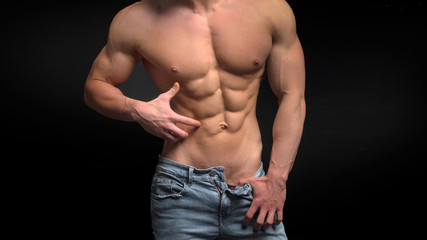 shirtless male torso with perfect abs. Man in blue jeans showing his abs