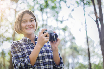 Beautiful girl learning to use film camera close to nature.