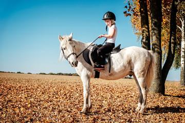 mädchen teitet auf weißen pony