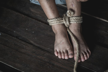 Stop violence Against Children, foot tied up with rope in emotional stress, The concept of stopping violence against children. Human rights Day concept. Anti-trafficking concept.