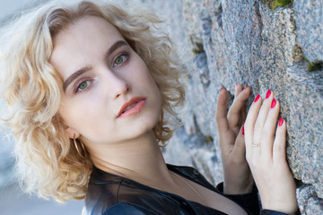 Blonde standing against a stone wall