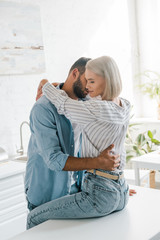 affectionate young couple hugging in kitchen, girlfriend sitting on kitchen counter