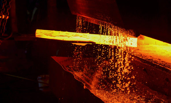 Hot iron in smeltery held by a worker. Melting of metal in a steel plant. High temperature in the melting furnace. Metallurgical industry. Factory for the manufacture of metal pipes.