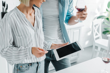 cropped image of couple using tablet with blank screen in kitchen