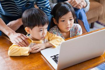 リビングでパソコンを囲む家族4人
