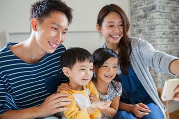 ソファーで写真を撮る家族4人