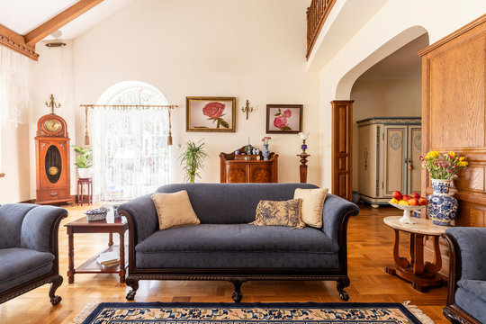 Cobalt blue sofa and other antique furniture on a wooden floor in a spacious living room interior of a classic mansion.