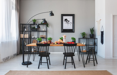 Black chairs and lamp at wooden table with food in grey dining room interior with poster. Real photo