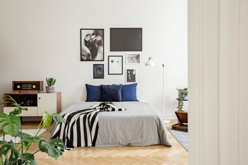 White wooden commode next to bed with dark blue pillows, grey duvet and striped black and white blanket in bedroom with framed art gallery on the wall. Real photo concept