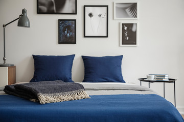 Close-up of bed with blue bedding and dark colored blanket. Bedside table with books and coffee next to it. Gallery of framed art on the wall. Real photo concept