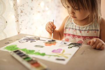 European child paints with watercolors, lifestyle