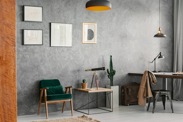 Armchair next to table under posters in grey freelancer's interior with chair at desk. Real photo